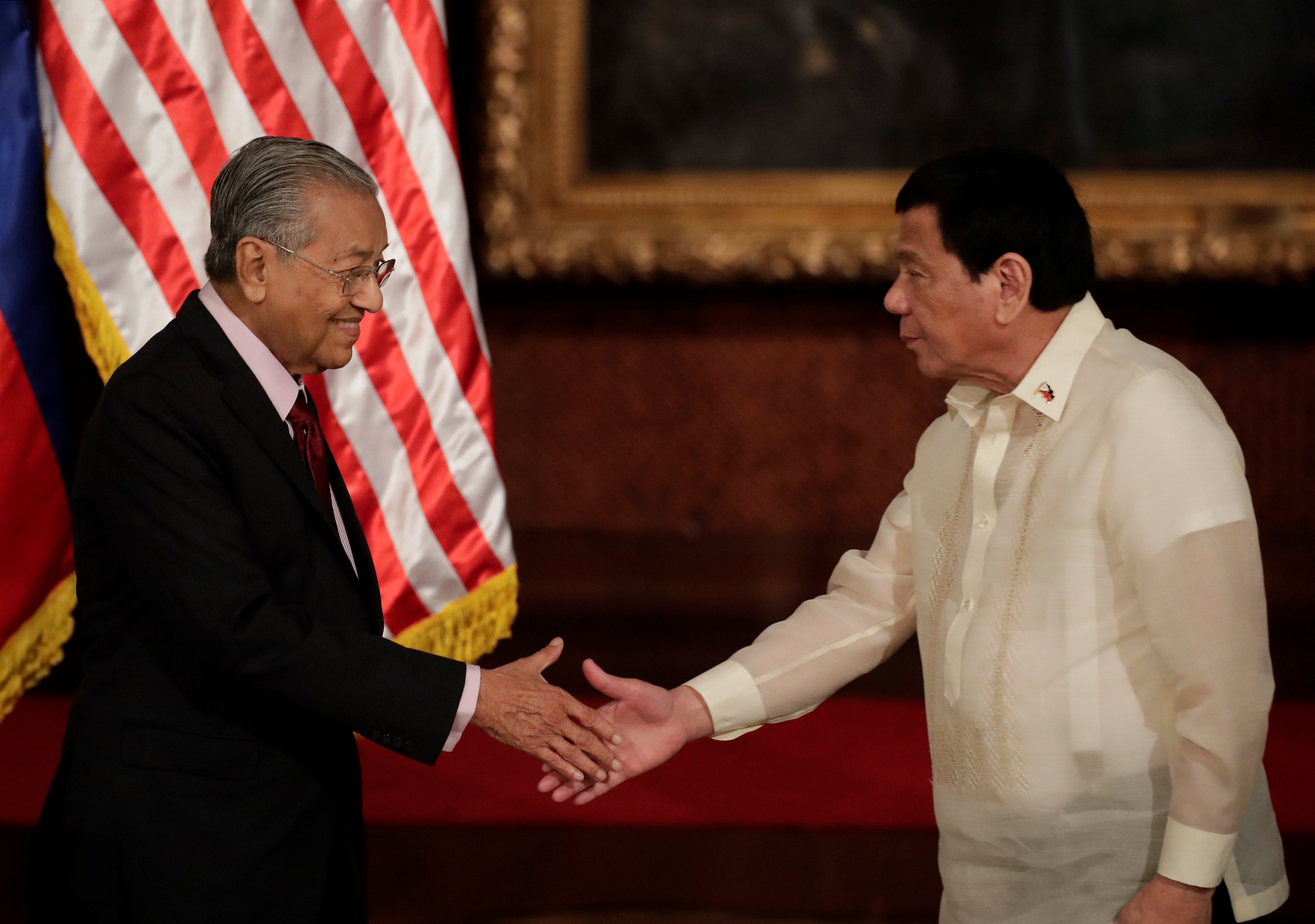 Philippine President Rodrigo Duterte and Malaysian Prime Mahathir Bin Mohamad watch a dance performance during the welcoming ceremony for the Malaysian leader at the Malacanang presidential palace in Manila