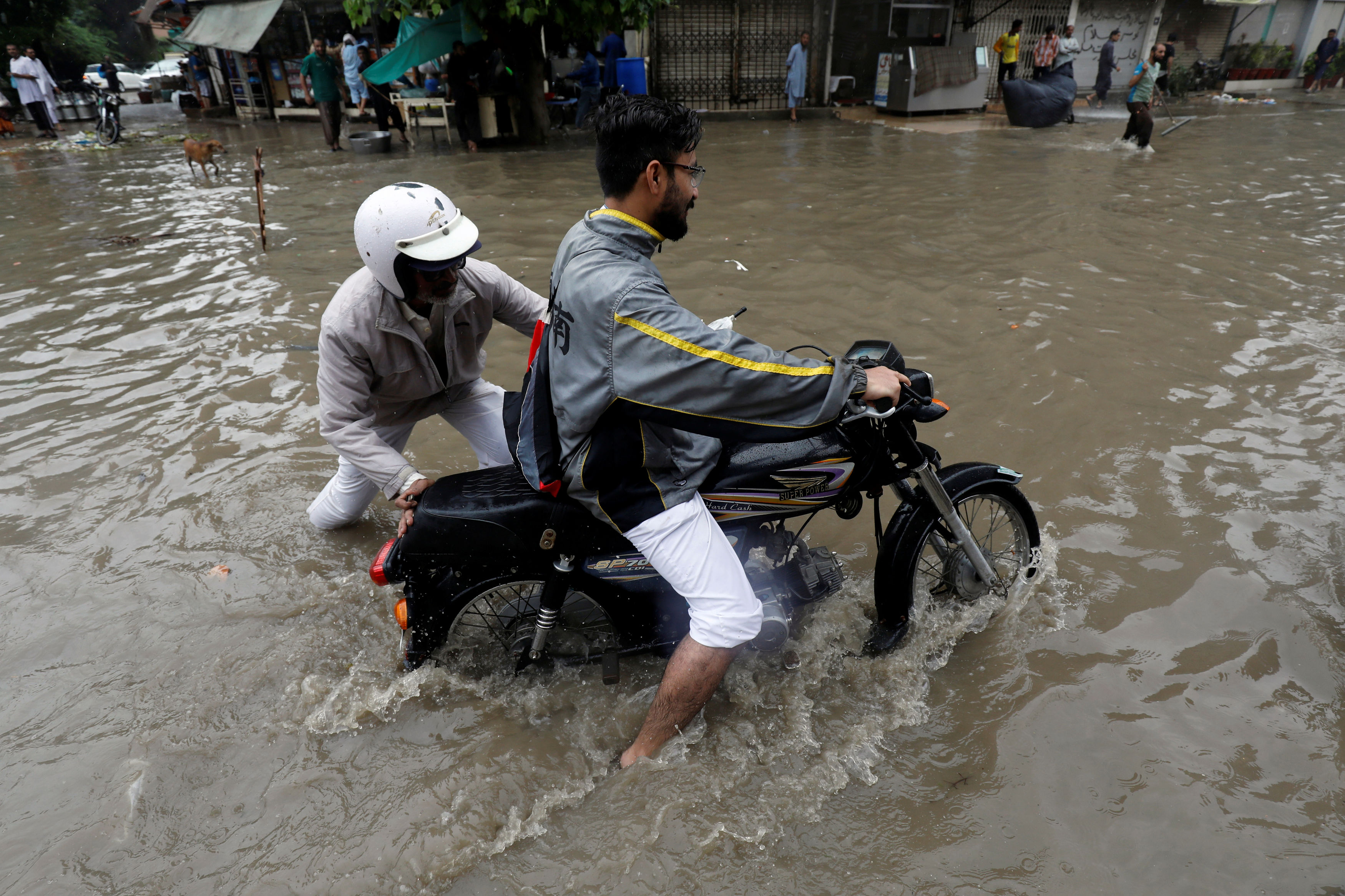 Traffic police officer helps a motorcyclist who is stuck in a ditch amid floodwater after heavy rain in Karachi