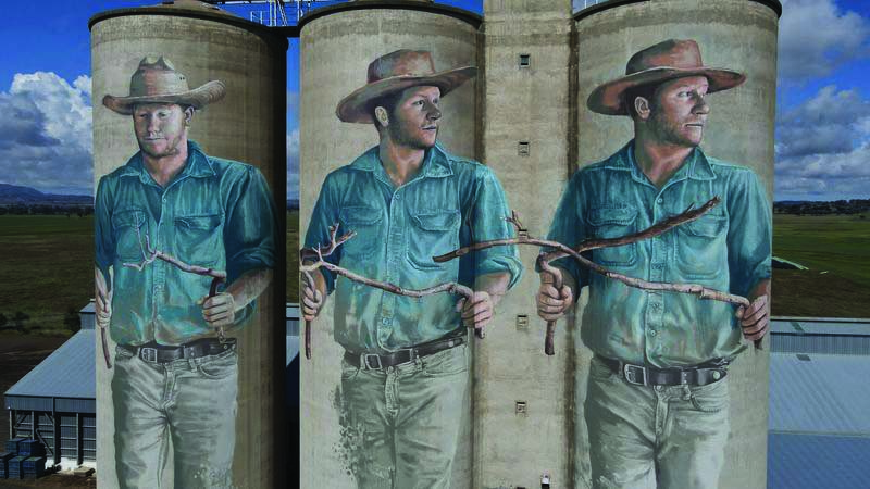 Painted depictions of a water diviner are seen on unused wheat silos in Barraba